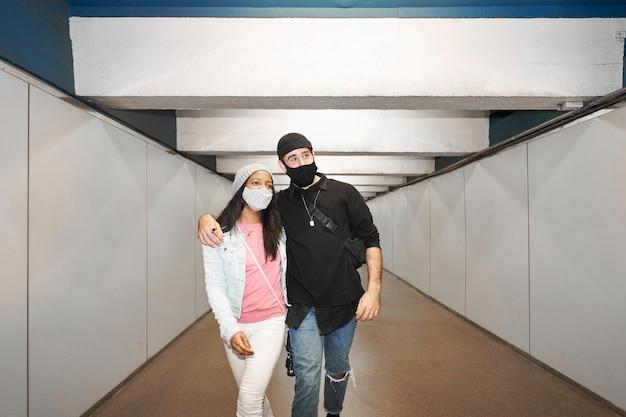 Молодые межрасовые пары влюбленных в коридоре метро. Premium Фотографии