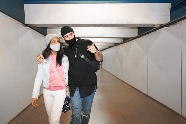 Молодая межрасовая пара влюбленных в коридоре подземного метро в масках для лица Premium Фотографии