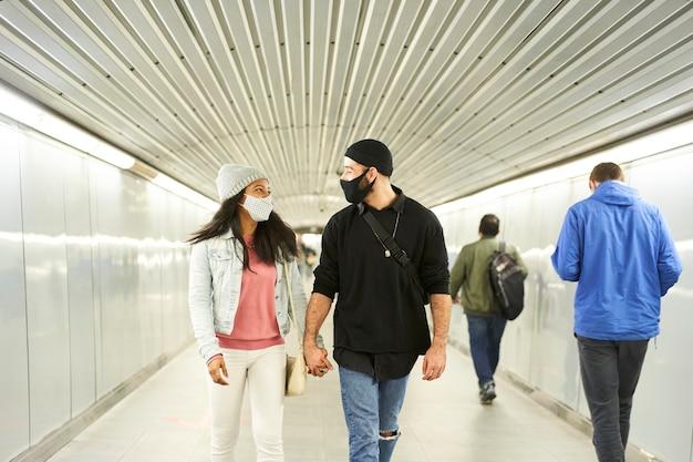 Young interracial couple walking hand in hand in an underground subway corridor. Premium Photo