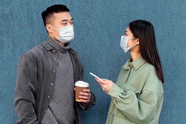 Giovane coppia giapponese che indossa la maschera Foto Gratuite