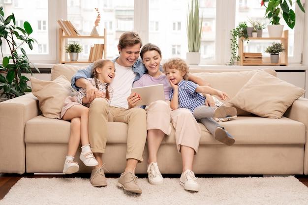 Молодая веселая повседневная семья из двух детей и пары, сидящей на диване и смотрящей смешное видео Premium Фотографии