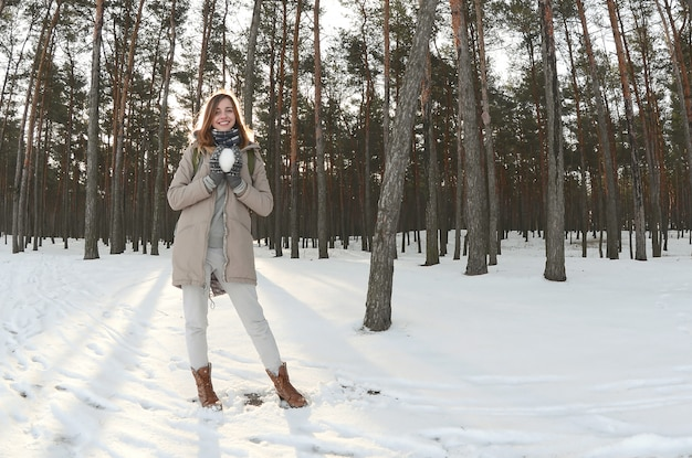 A young and joyful caucasian girl in a brown coat holds a snowball in a snow-covered forest in winter. fisheye photo Premium Photo