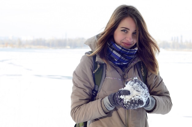 A young and joyful caucasian girl in a brown coat holds a snowball Premium Photo
