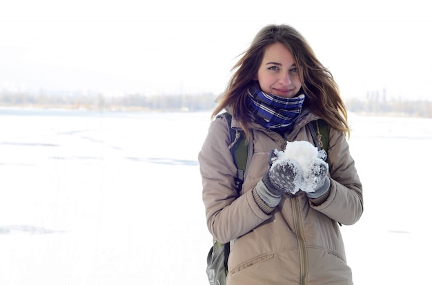 A young and joyful caucasian girl in a brown coat in the snow Premium Photo