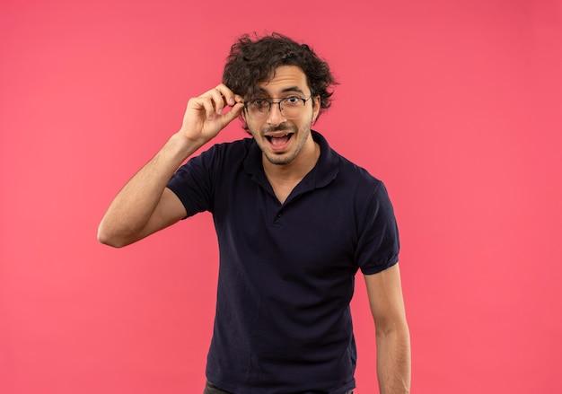Giovane uomo gioioso in camicia nera con occhiali ottici tiene occhiali e sembra isolato sulla parete rosa Foto Gratuite