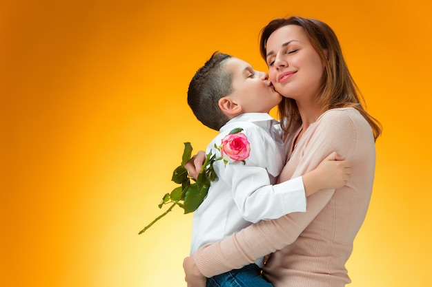 Young kid giving red rose to his mom Free Photo