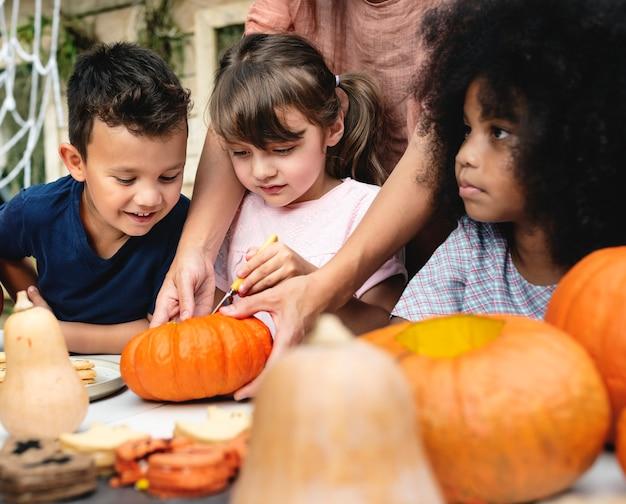 Young kids carving halloween jack-o-lanterns Free Photo