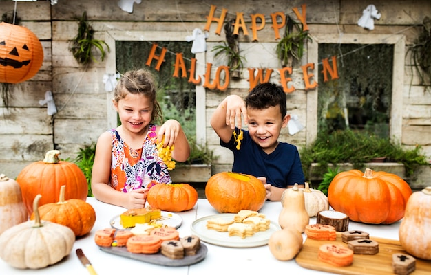 Young kids carving halloween jack-o-lanterns Free Photo