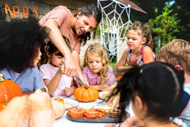 Young kids carving halloween jack-o-lanterns Premium Photo
