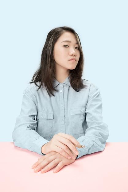 스튜디오에서 테이블에 앉아있는 동안 시가 흡연 젊은 한국 여성. 무료 사진