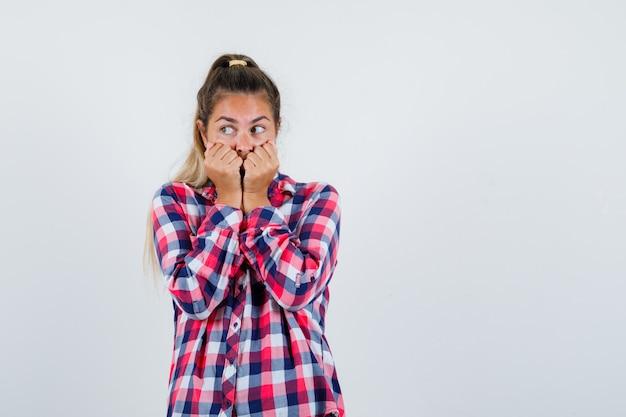 Giovane donna in camicia a quadri tenendo i pugni sulla bocca e guardando spaventata, vista frontale. Foto Gratuite