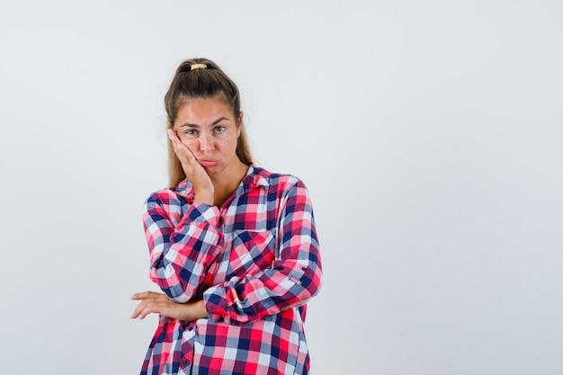 Giovane donna in camicia a quadri appoggiata sulla guancia sul palmo e guardando abbattuto, vista frontale. Foto Gratuite