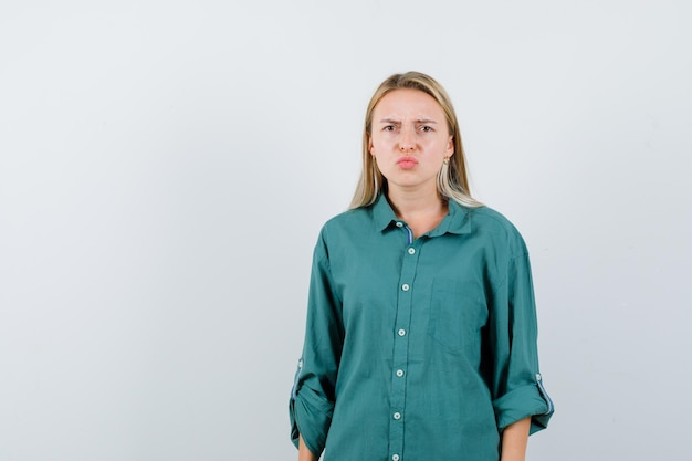 Young lady curving lips in green shirt and looking gloomy Free Photo