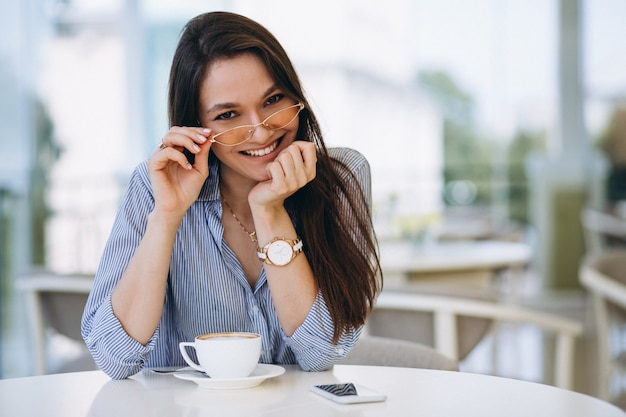 Young lady drinking tea in a cafe Free Photo