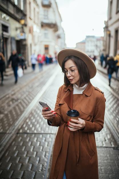 若い女性はビデオ通話をしていて、街の屋外を歩きながらコーヒーを飲む 無料写真