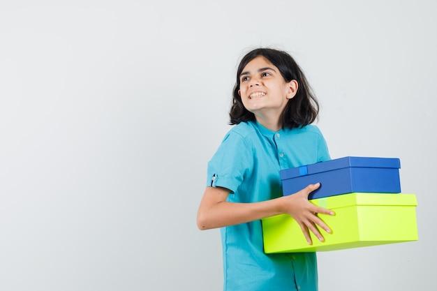 파란색 셔츠에 색된 선물 상자를 들고 기쁜 찾고 젊은 아가씨. 무료 사진