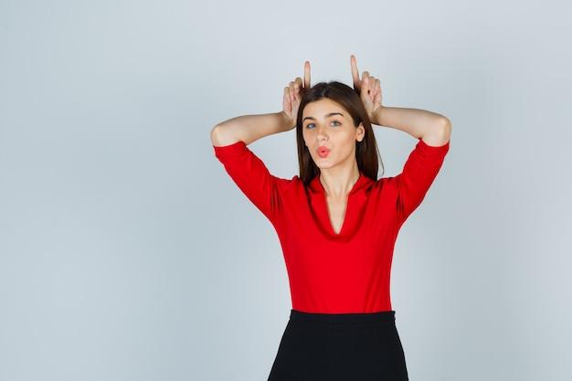 Giovane donna che tiene le dita sopra la testa come corna di toro in camicetta rossa, gonna e sembra divertente Foto Gratuite
