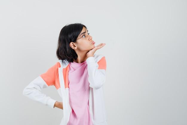 Giovane donna che tiene la mano alla mascella mentre guarda da parte in giacca, camicia rosa e sembra strana. Foto Gratuite