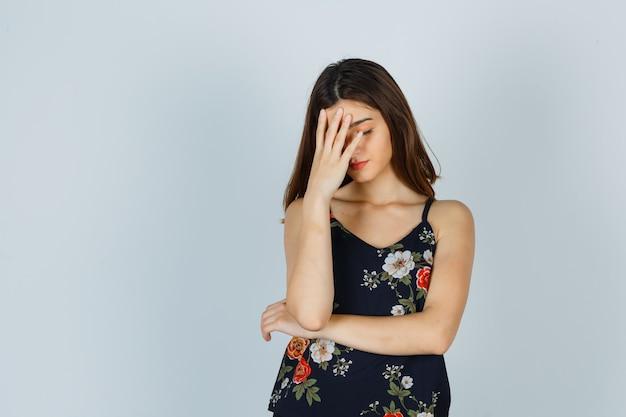 花のトップで顔に手をつないで疲れている若い女性 無料写真