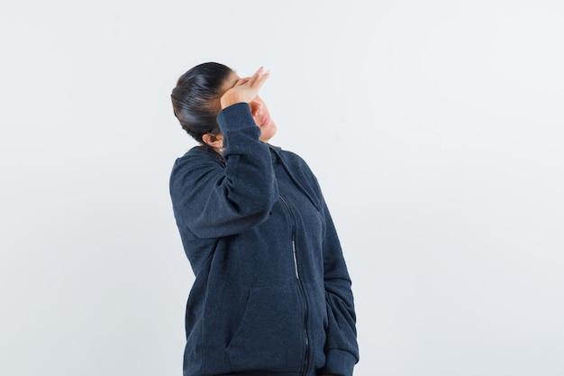 재킷에서 멀리보고 초점을 맞춘 동안 그녀의 이마에 손을 잡고 젊은 아가씨. 전면보기. 무료 사진