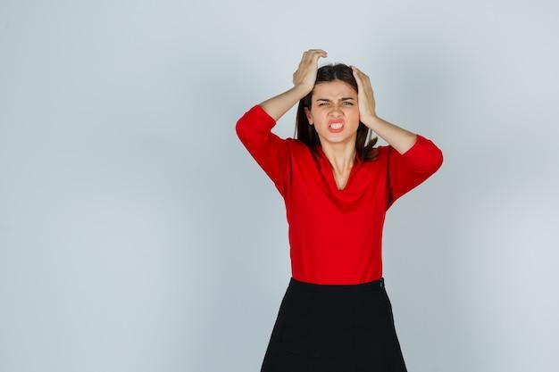 빨간 블라우스, 치마에 머리에 손을 잡고 피곤 찾고 젊은 아가씨 무료 사진