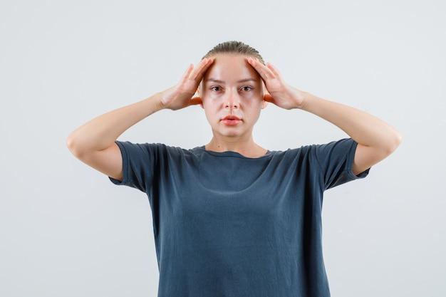 Девушка в серой футболке держит руки над головой и смотрит осторожно Бесплатные Фотографии