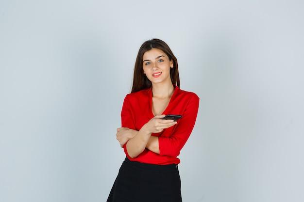 Giovane signora che tiene il telefono cellulare mentre posa in camicetta rossa, gonna e sembra allegra Foto Gratuite