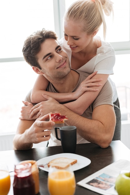 Young lady hug her man while they have breakfast Free Photo