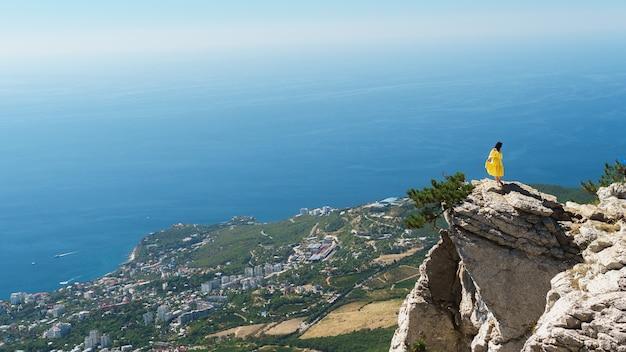 Барышня в желтом платье стоит на скале на фоне города у синего моря. романтическая концепция. Premium Фотографии