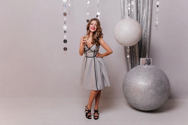 美しいデザイナーのドレスとかかとの黒い靴で、クリスマスの装飾に対して、白いスパークリングワインのガラスでポーズをとる若い女性 無料写真