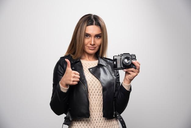 긍정적이고 웃는 방식으로 카메라로 사진을 찍는 검은 가죽 재킷에 젊은 아가씨. 무료 사진