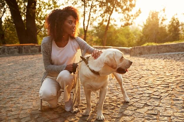 座っていると公園で犬を抱いてカジュアルな服装の若い女性 無料写真