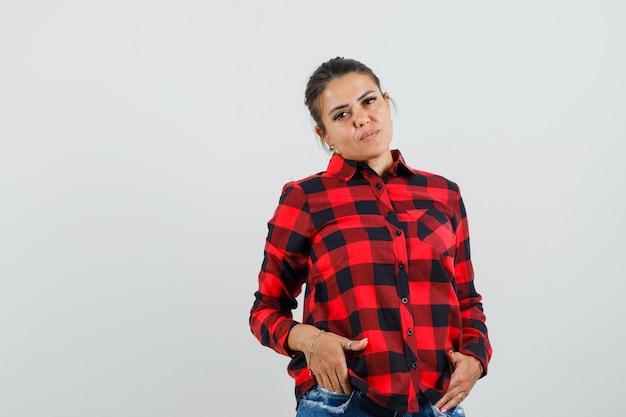 체크 셔츠에 젊은 아가씨, 반바지 주머니에 손을 잡고 자신감을 찾고 무료 사진