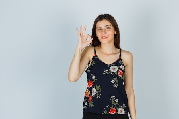 フローラルトップの若い女性は、okのジェスチャーを示し、満足そうに見えます 無料写真