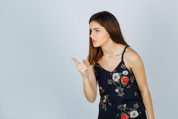 花のトップの若い女性は、警告のジェスチャーを示しています 無料写真