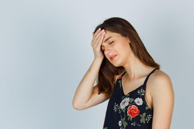 두통으로 고통 받고, 옆으로 서서 화가 찾고 꽃 상단에 젊은 아가씨. 무료 사진
