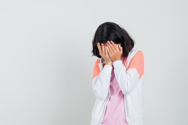 ジャケットを着た若い女性、彼女の顔に手をつないで悲しそうに見えるピンクのシャツ 無料写真