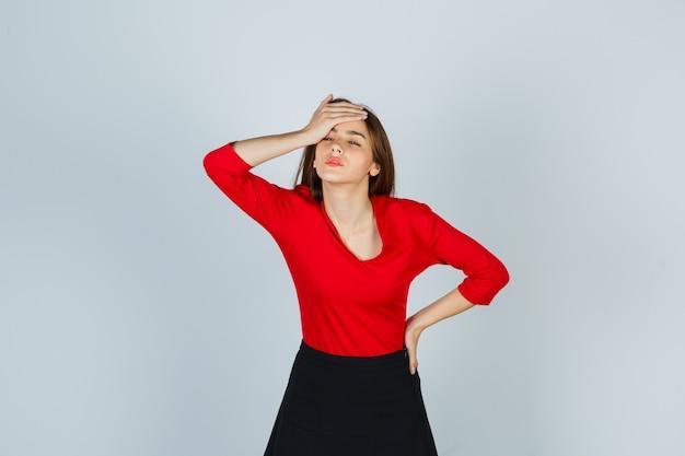 빨간 블라우스에 젊은 아가씨, 손을 유지하면서 이마에 손을 잡고 치마 무료 사진