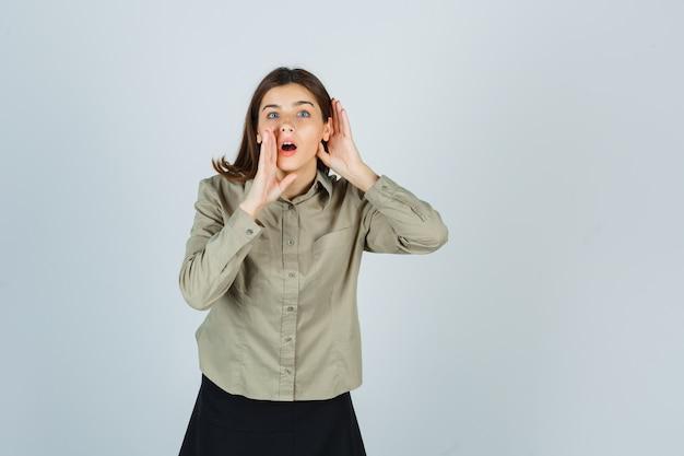 シャツを着た若い女性、耳の後ろと口の近くで手をつないで秘密を告げるスカート 無料写真