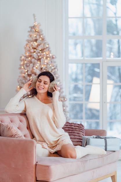 Молодая леди в белом платье на диване во время рождества Бесплатные Фотографии