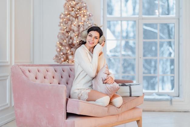 크리스마스 시간에 소파에 하얀 드레스를 입고 젊은 아가씨 무료 사진