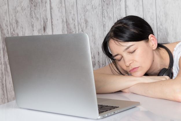 Барышня в белой рубашке с черными наушниками уснула перед ноутбуком на сером Бесплатные Фотографии