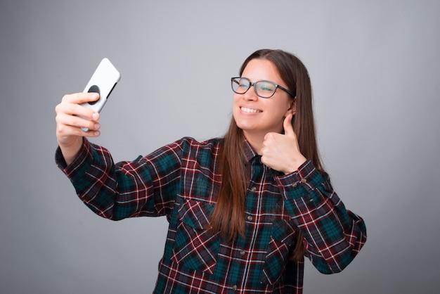 Девушка делает селфи со своим телефоном на сером фоне. Premium Фотографии