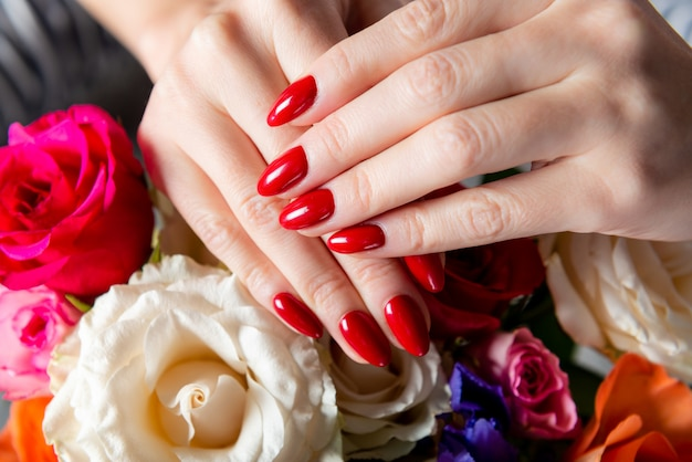 Young lady is showing her red manicure nails Premium Photo