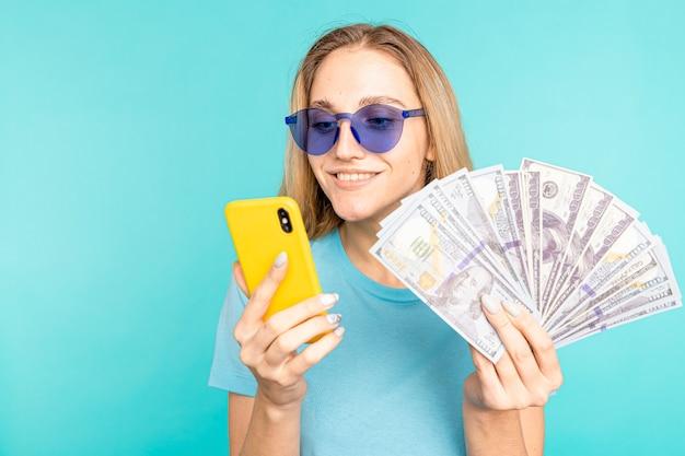 若い女性は青い背景で隔離。お金を持っている携帯電話のディスプレイを示すカメラを見てください。 Premium写真