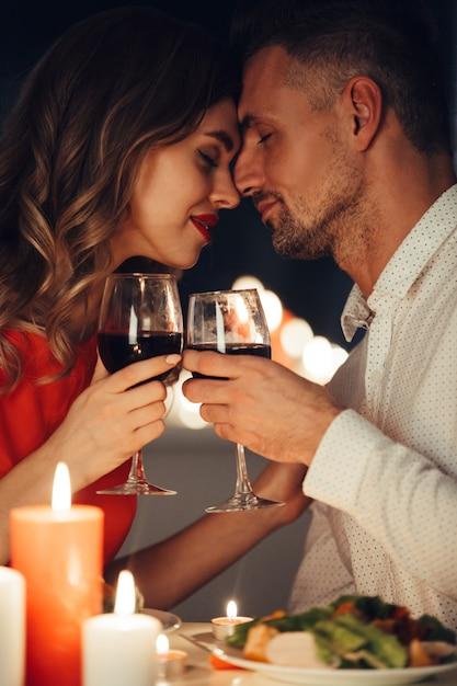 Барышня целует своего шикарного мужчину во время романтического ужина Бесплатные Фотографии
