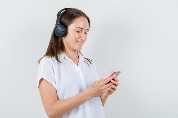 白いブラウスで携帯電話を見ながら陽気に音楽を聴いている若い女性。 無料写真