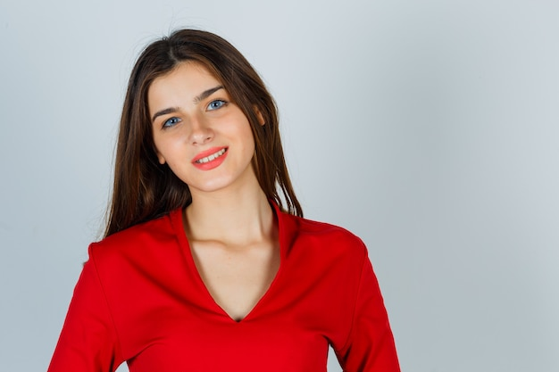 빨간 블라우스에 카메라를보고 매혹적인 찾고 젊은 아가씨 무료 사진