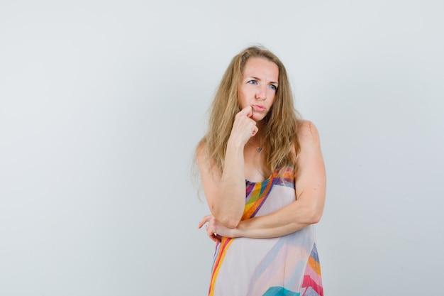 Giovane donna che guarda lontano con il mento appoggiato a portata di mano in abito estivo e guardando pensieroso. Foto Gratuite