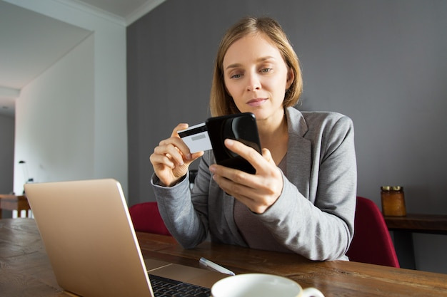 Young lady making online payment using smartphone Free Photo